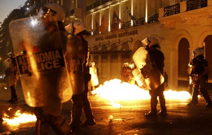 Riot police stand amongst the flames from exploded petrol bombs thrown by a small group of anti-austerity demonstrators in front of parliament in Athens, Greece July 15, 2015. REUTERS/Yannis Behrakis
