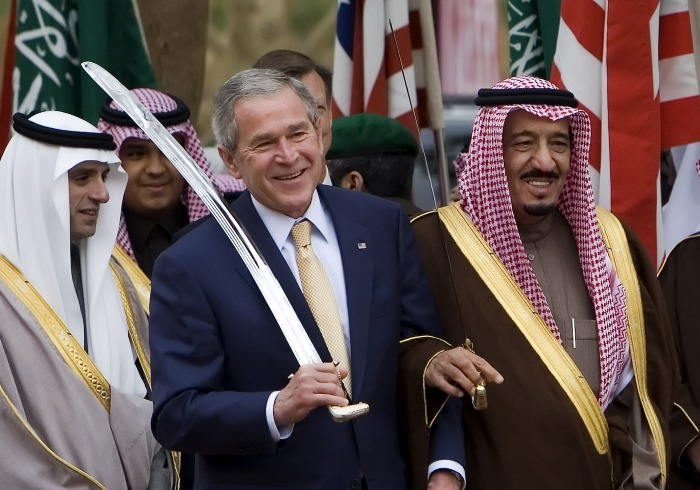 US President George W. Bush dances with a sword with Prince Salman bin Abdul Aziz (R), the brother of the Saudi king and Governor of Riyadh, during their tour of the Murabba Palace and National History History Museum in the Saudi capital, 15 January 2008. Bush holds a second day of talks in Saudi Arabia after his administration announced it was taking the first steps in a multi-billion-dollar arms deal with the kingdom. AFP PHOTO/JIM WATSON